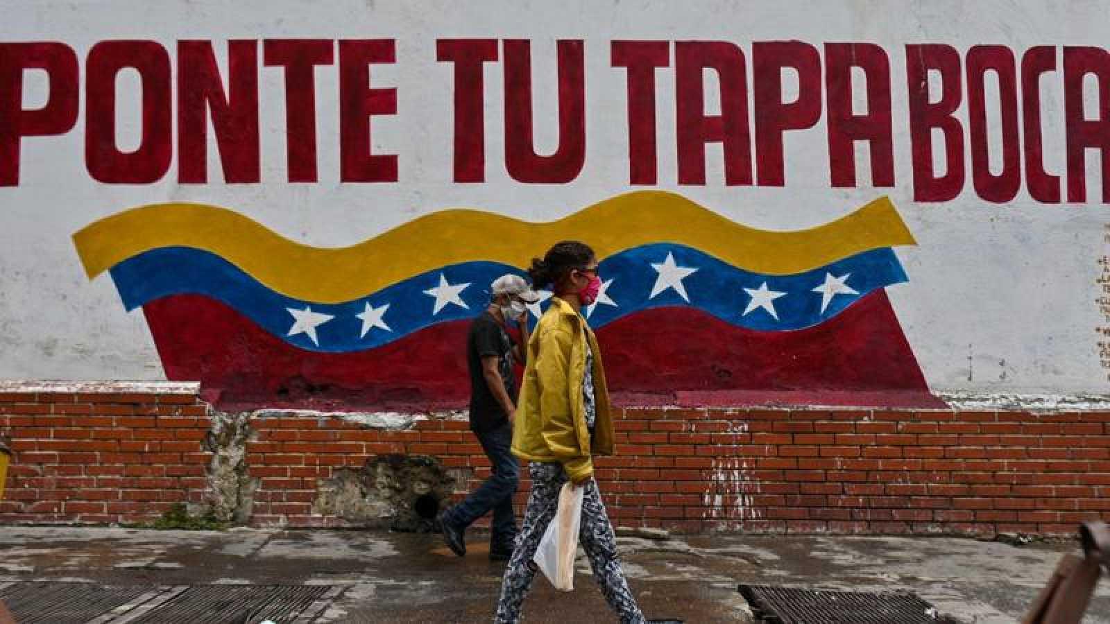 Dos personas caminan por una calle del centro de Caracas