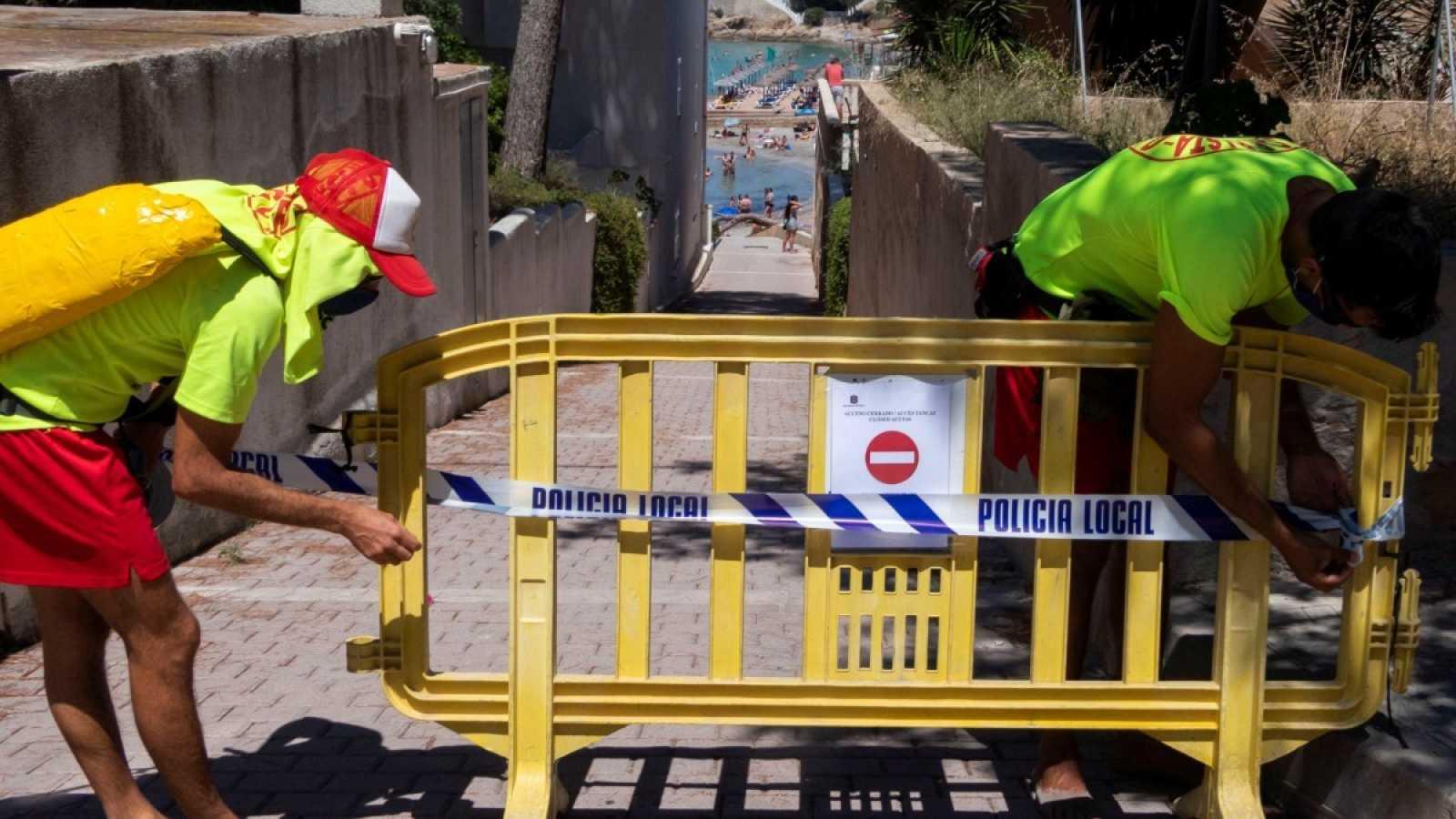 Dos socorristas vallan uno de los accesos a la playa pequeña de Sant Elm, en Mallorca