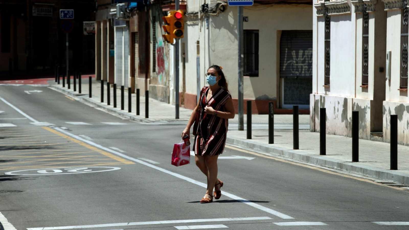 Una mujer con mascarilla pasea por una calle de Barcelona