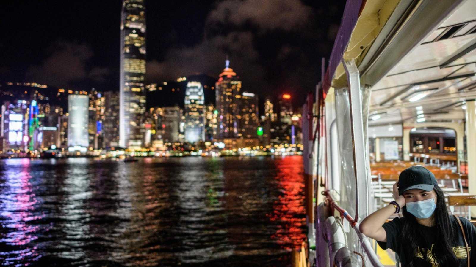 Una mujer con mascarilla cruza el puerto en el ferry de Hong Kong