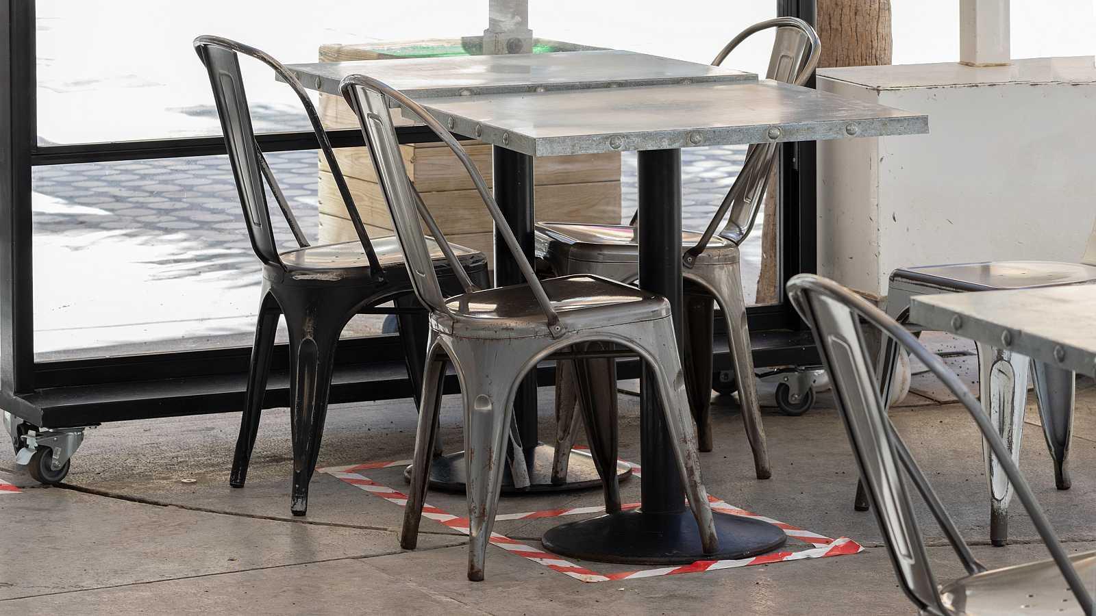 Sillas y mesas vacías en una terraza de bar con el suelo señalizado para mantener la distancia social.