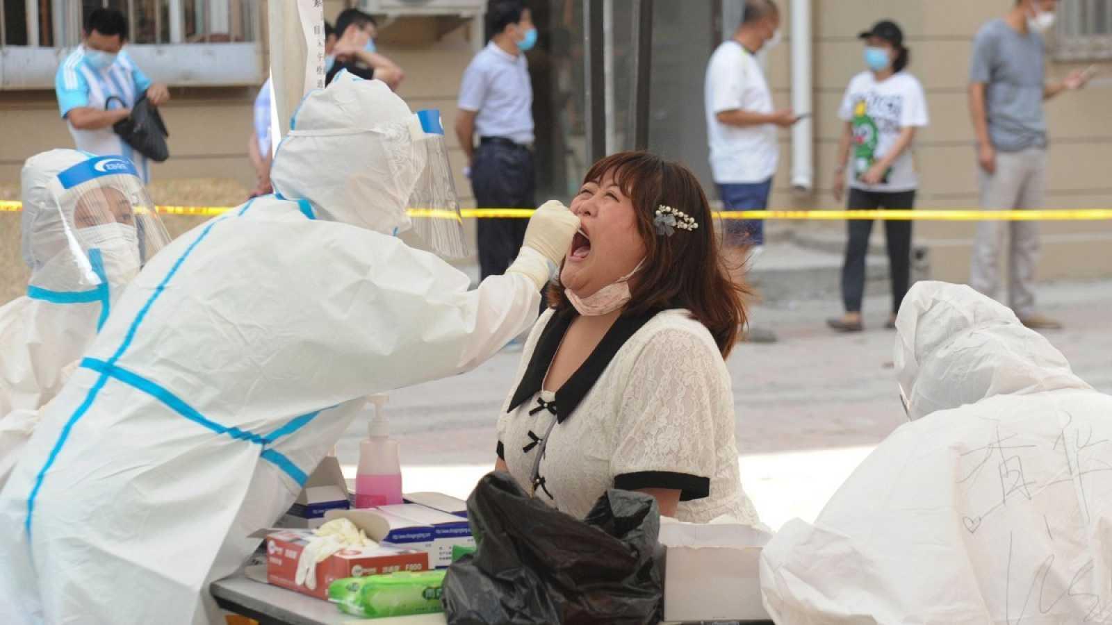 Un sanitario realiza una prueba de coronavirus a una residente en un centro de pruebas improvisado en Dalian, en la provincia nororiental de Liaoning en China