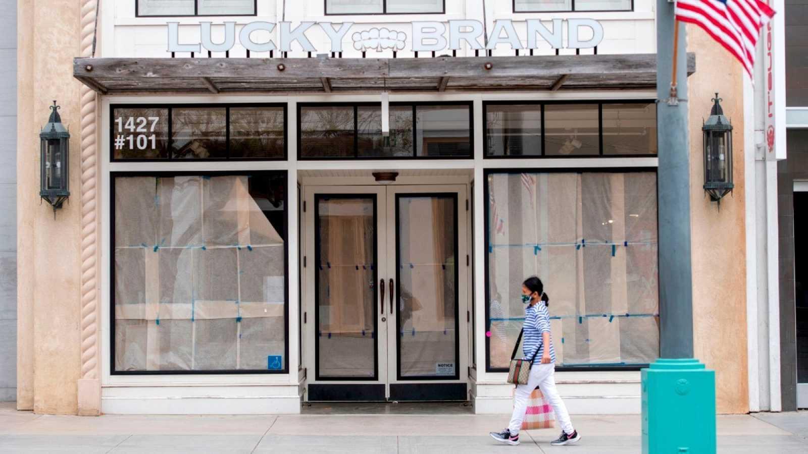 Una viandante con mascarilla pasa por delante de una tienda cerrada en Santa Mónica, California, durante la pandemia de coronavirus en Estados Unidos