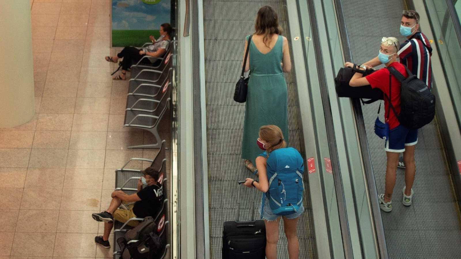 Viajeros con máscaras sanitarias caminan este miércoles por la Terminal 1 del aeropuerto Josep Tarradelles - El Prat, en Barcelona.
