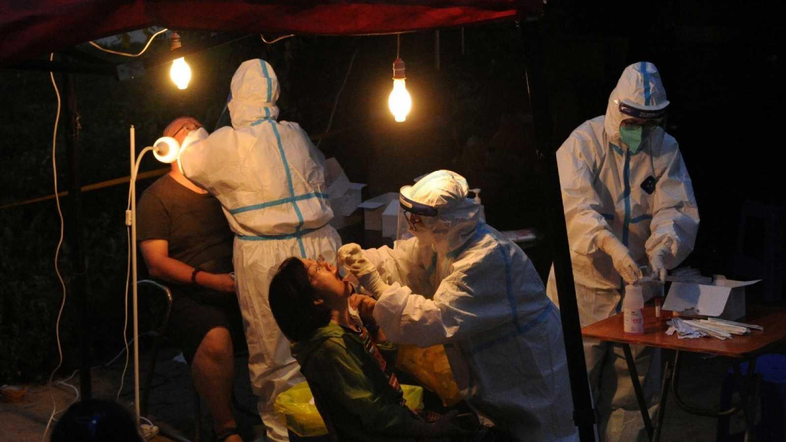 Sanitarios con trajes de protección realizan pruebas del coronavirus en Dalian, en la provincia de Liaoning, China, esta semana.