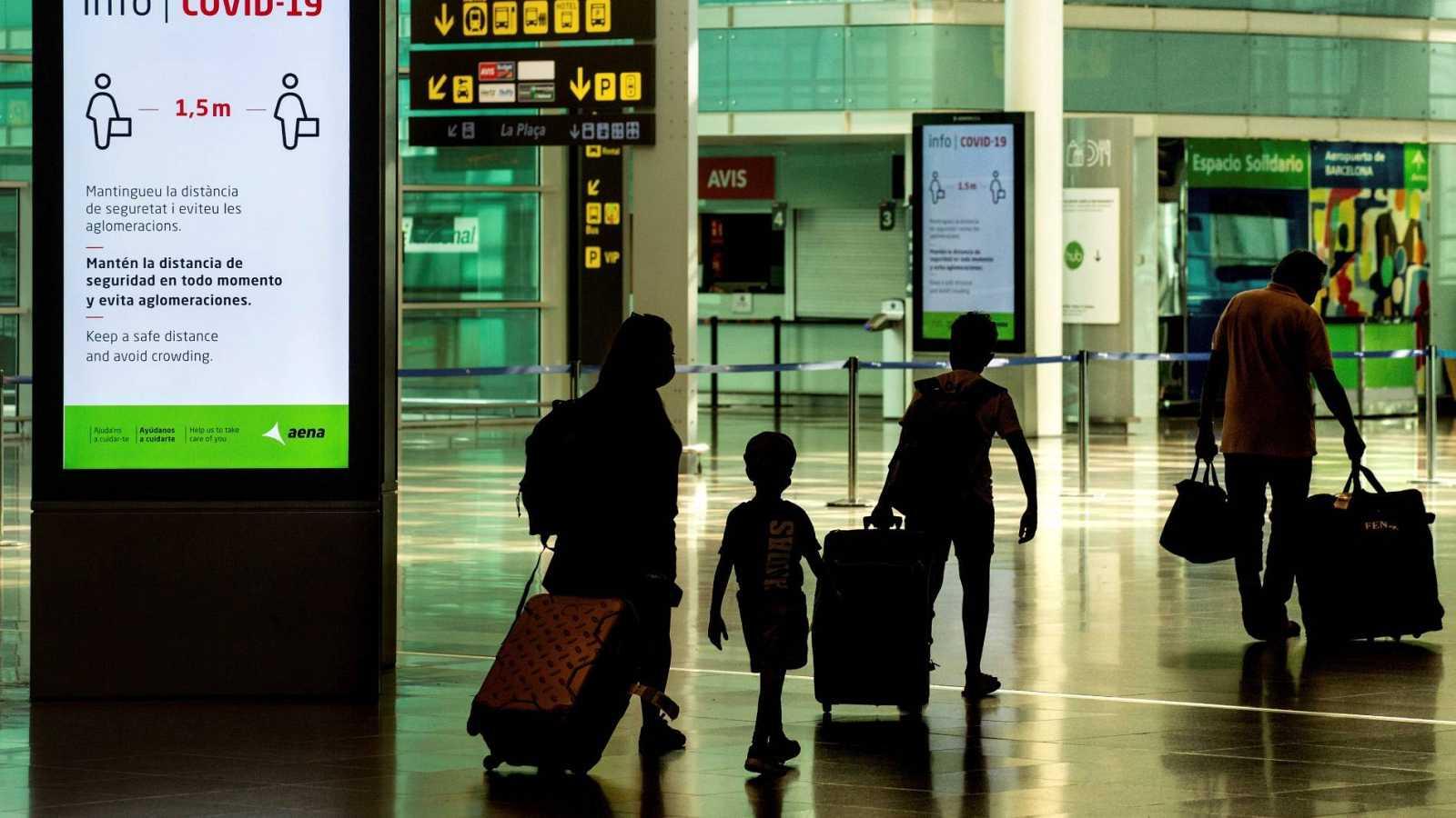 Viajeros con máscaras sanitarias caminan este miércoles por la Terminal 1 del aeropuerto Josep Tarradelles - El Prat, en Barcelona