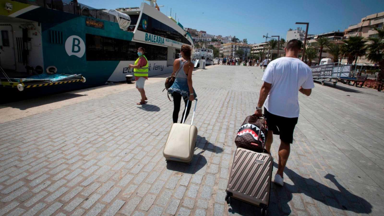Dos turistas con maleta se disponen a coger un crucero