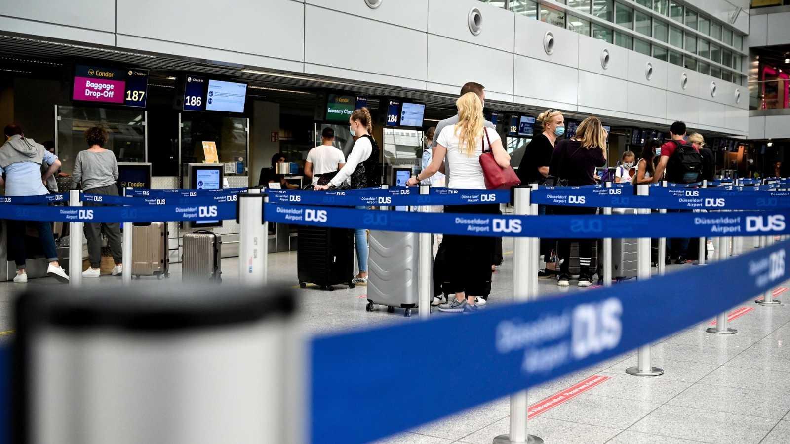 Viajeros esperan en la zona de facturación del aeropuerto de Dusseldorf, Alemania.