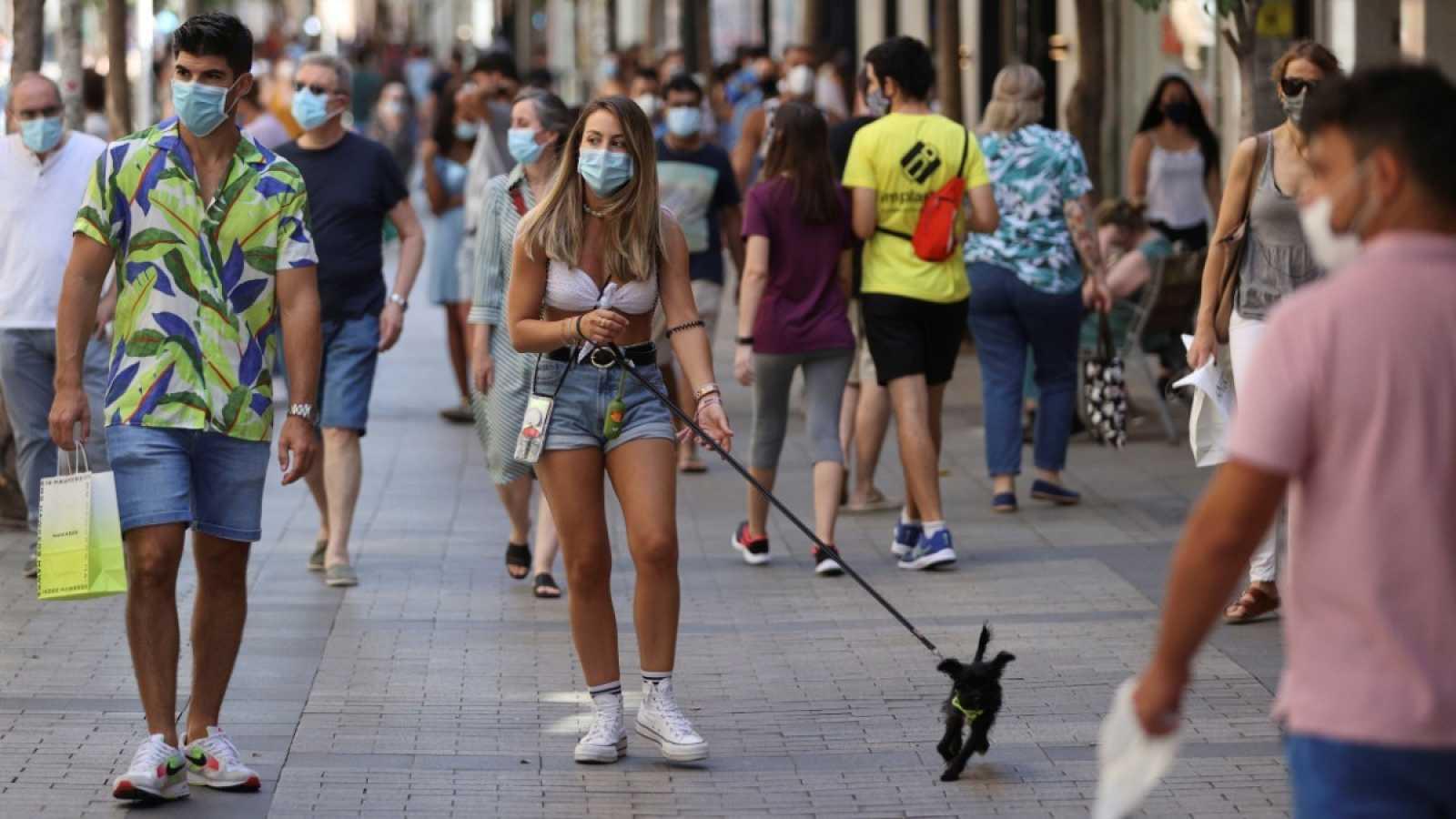 Una chica pasea con su perro en un transitada calle de Madrid
