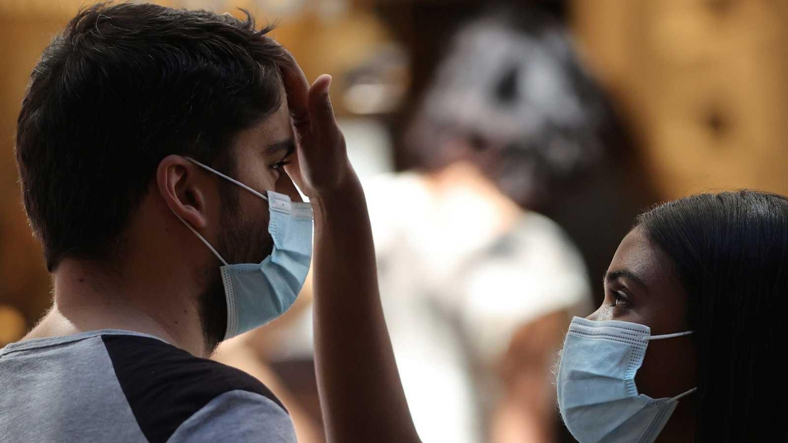 Pareja de jóvenes con mascarillas en Madrid durante la ola de calor