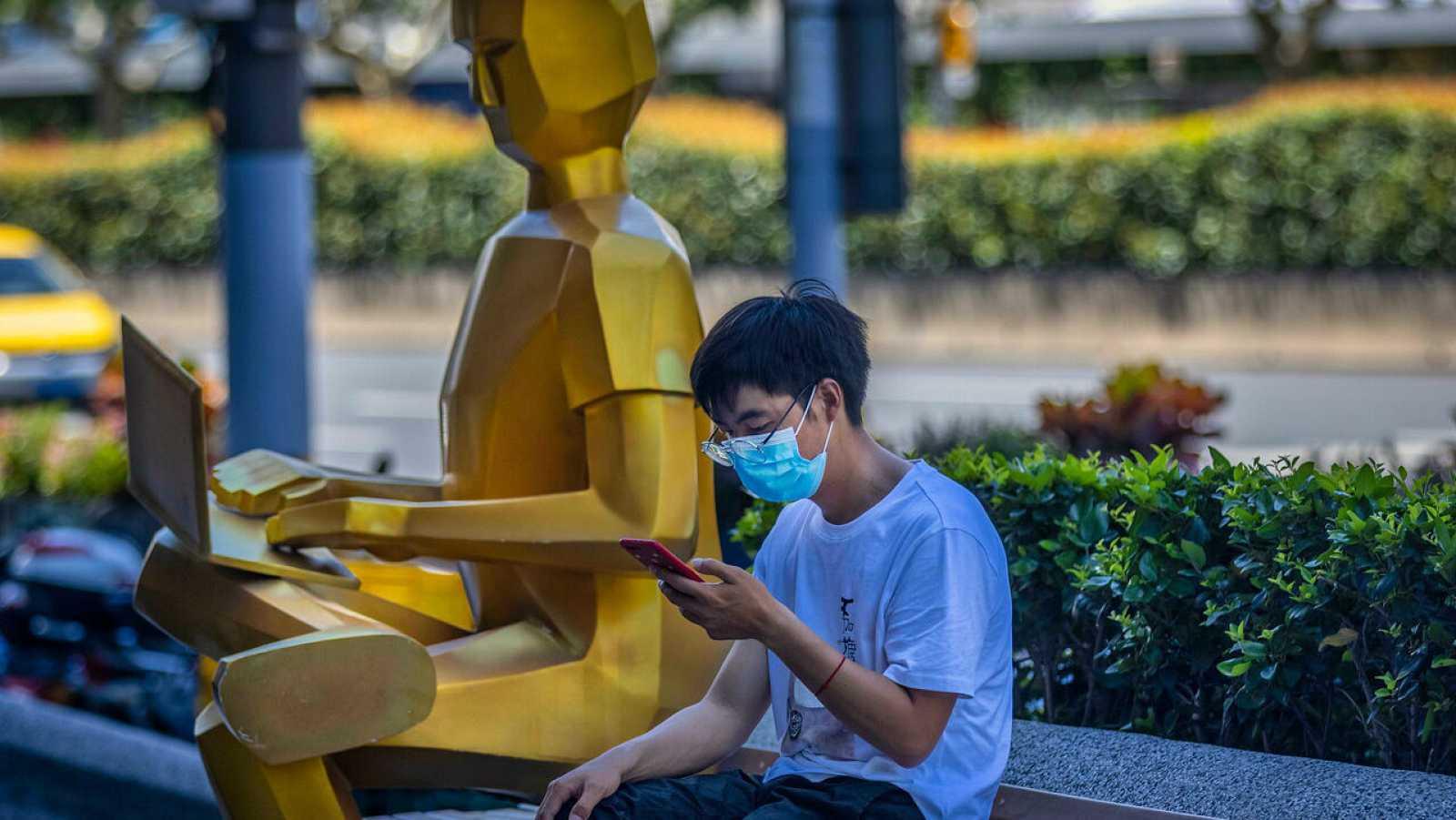 Un hombre usa su teléfono junto a una escultura en Shanghai, China.