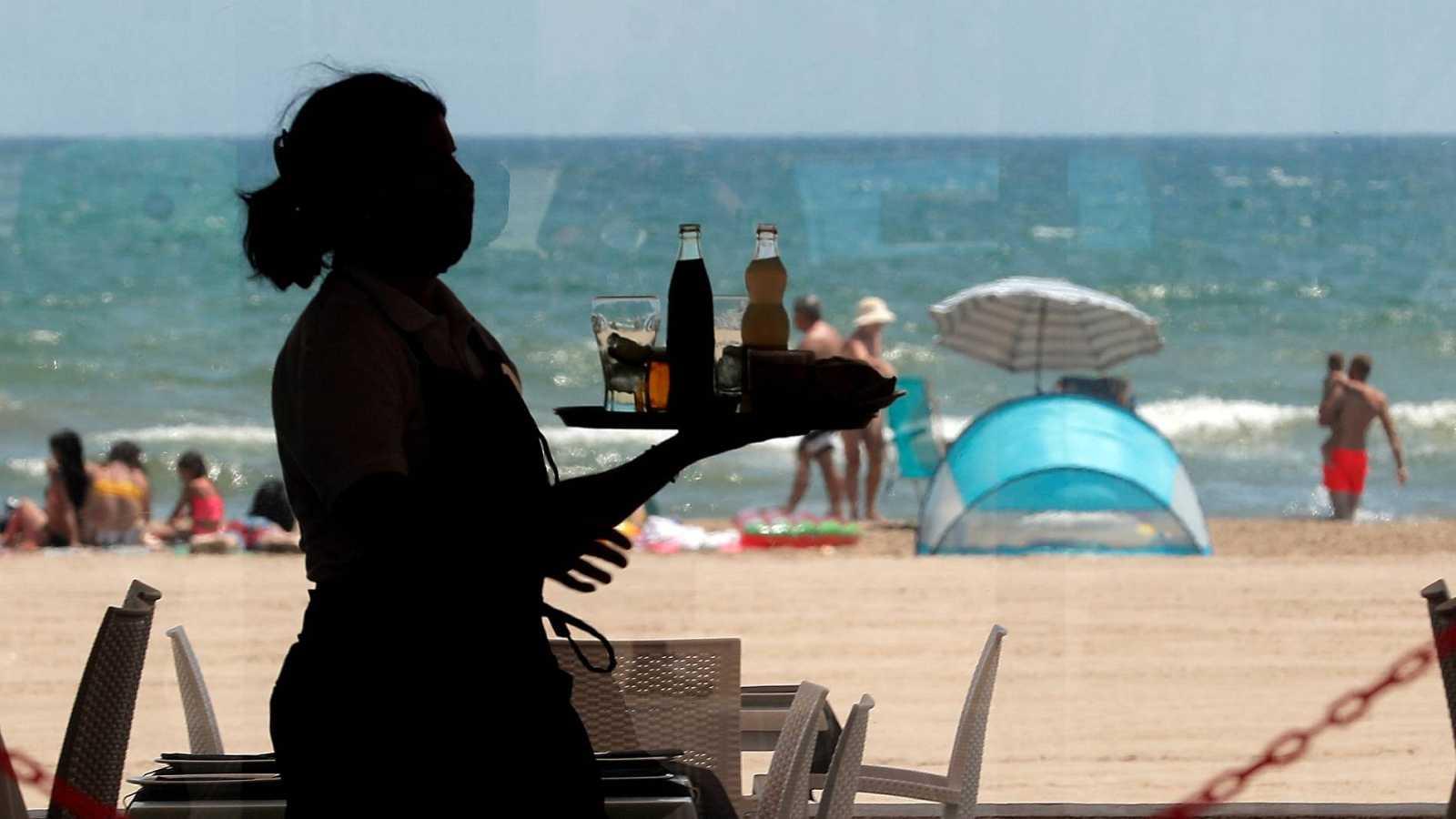 Una camarera lleva una bandeja con bebidas en un restaurante de la playa de la Malvarrosa, en Valencia