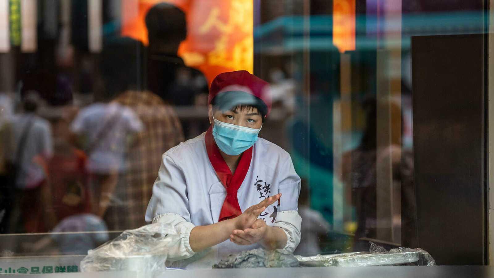 Una mujer con mascarilla hace bolas de masa en un escaparate en Shanghai, China.