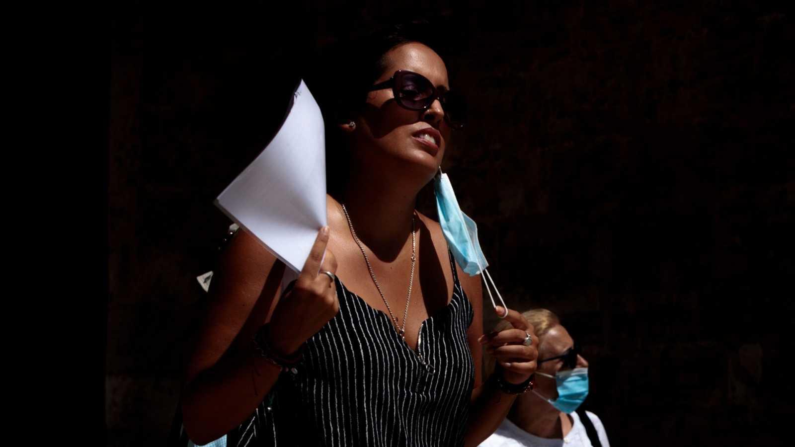 Una persona se abanica con unos documentos en una calle del centro de Valencia.