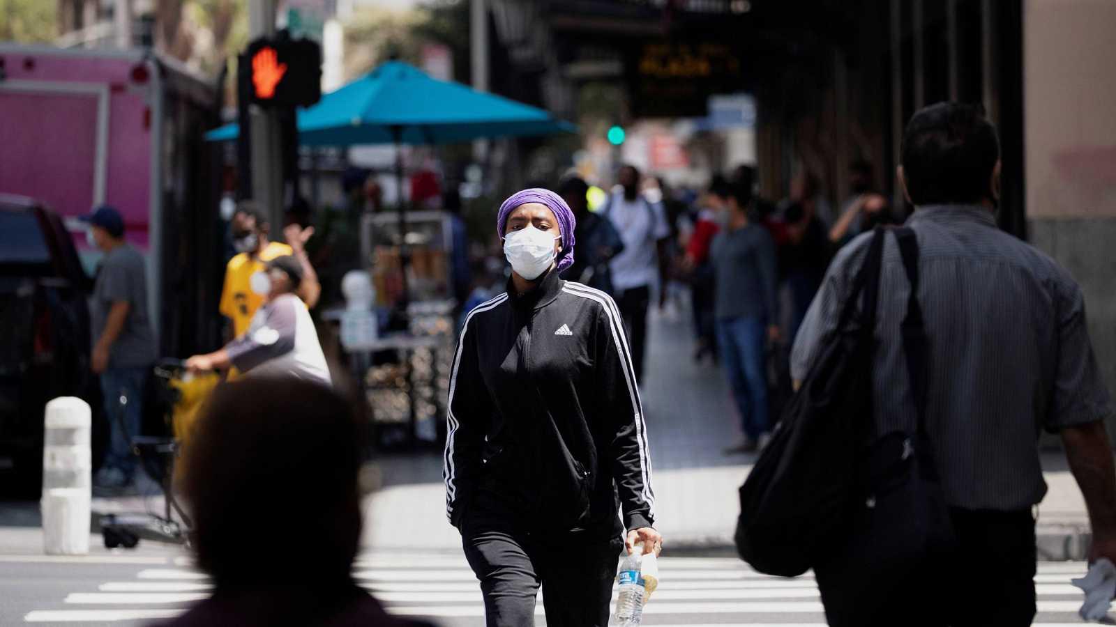 Una mujer con mascarilla cruza una calle en Los Ángeles