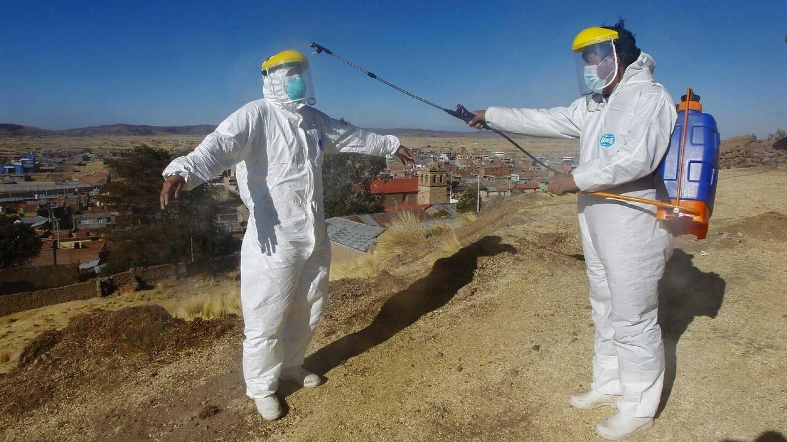 Empleados de la funeraria se preparan para el entierro de un fallecido con coronavirus en Acora, Perú. Carlos MAMANI / AFP.