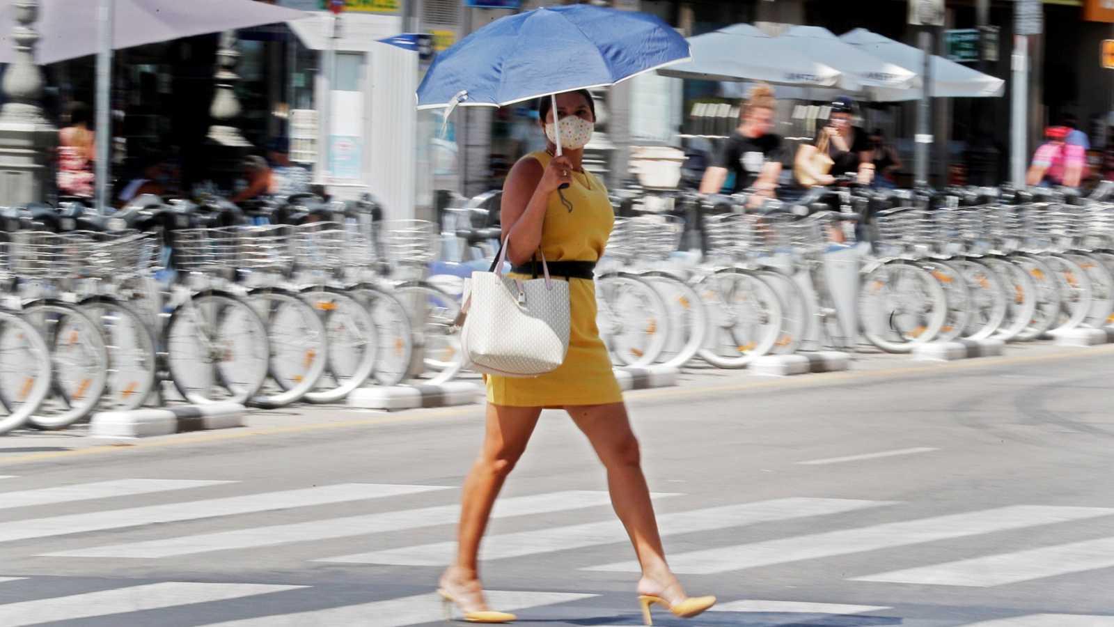 Una persona se protege del calor con una sombrilla en la ciudad de Valencia