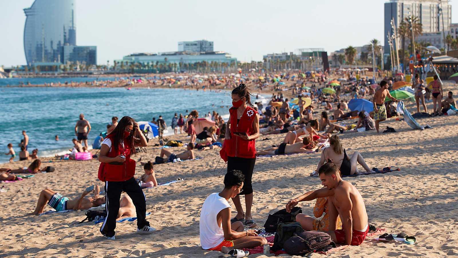 Miembros de Cruz Roja, durante una campaña de concienciación de contagios, en la Barceloneta.