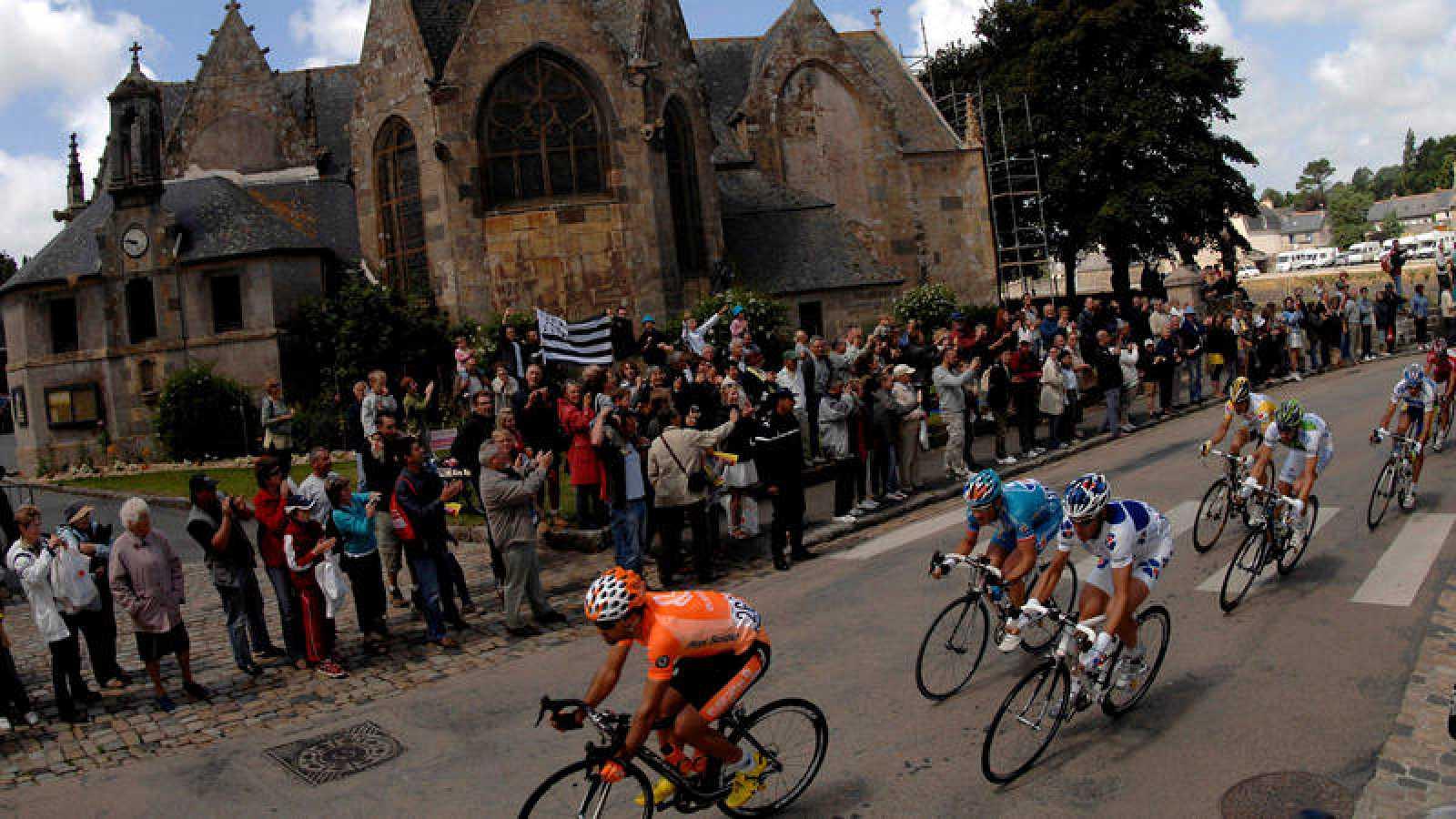 Un grupo de aficionados con una bandera bretona al paso de los ciclistas por delante de una iglesia durante el Tour 2008