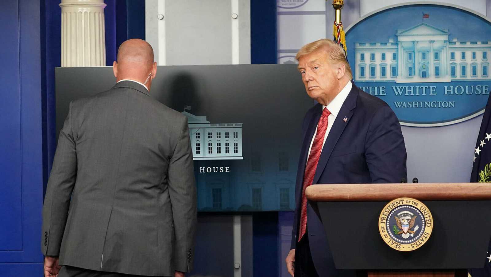 El presidente de los Estados Unidos, Donald Trump, abandona una rueda de prensa sobre la pandemia de coronavirus en la Casa Blanca, en Washington, acompañado por un agente del Servicio Secreto de EE.UU.