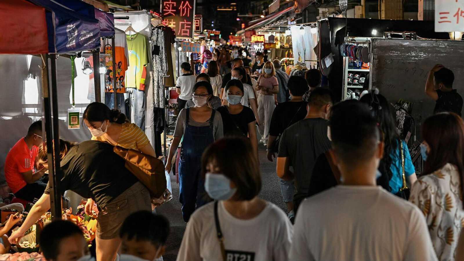 Personas caminando por un mercado nocturno en Wuhan, en la provincia central de Hubei, en China.