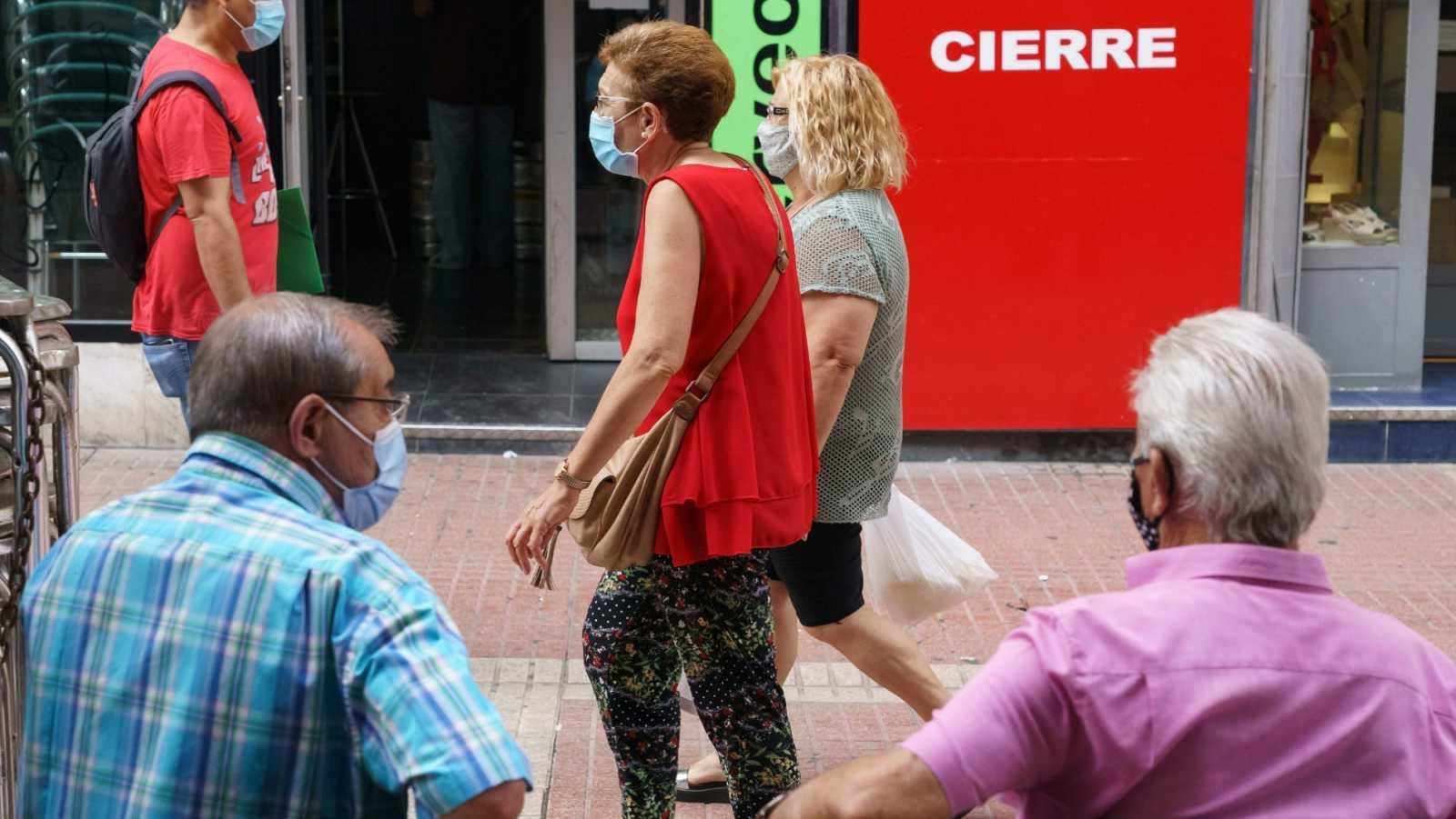 Varias personas pasean por el barrio de las Delicias de Zaragoza