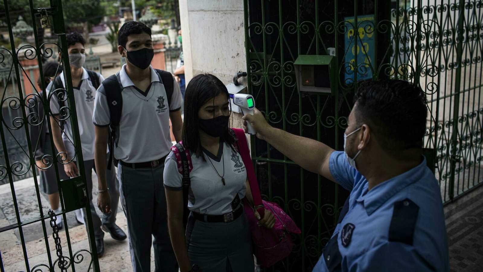 Un guardia le toma la temperatura a los estudiantes hoy durante el inicio de clases en el Colegio Amazonense Dom Pedro II, en el centro de Manaos, Amazonas (Brasil).