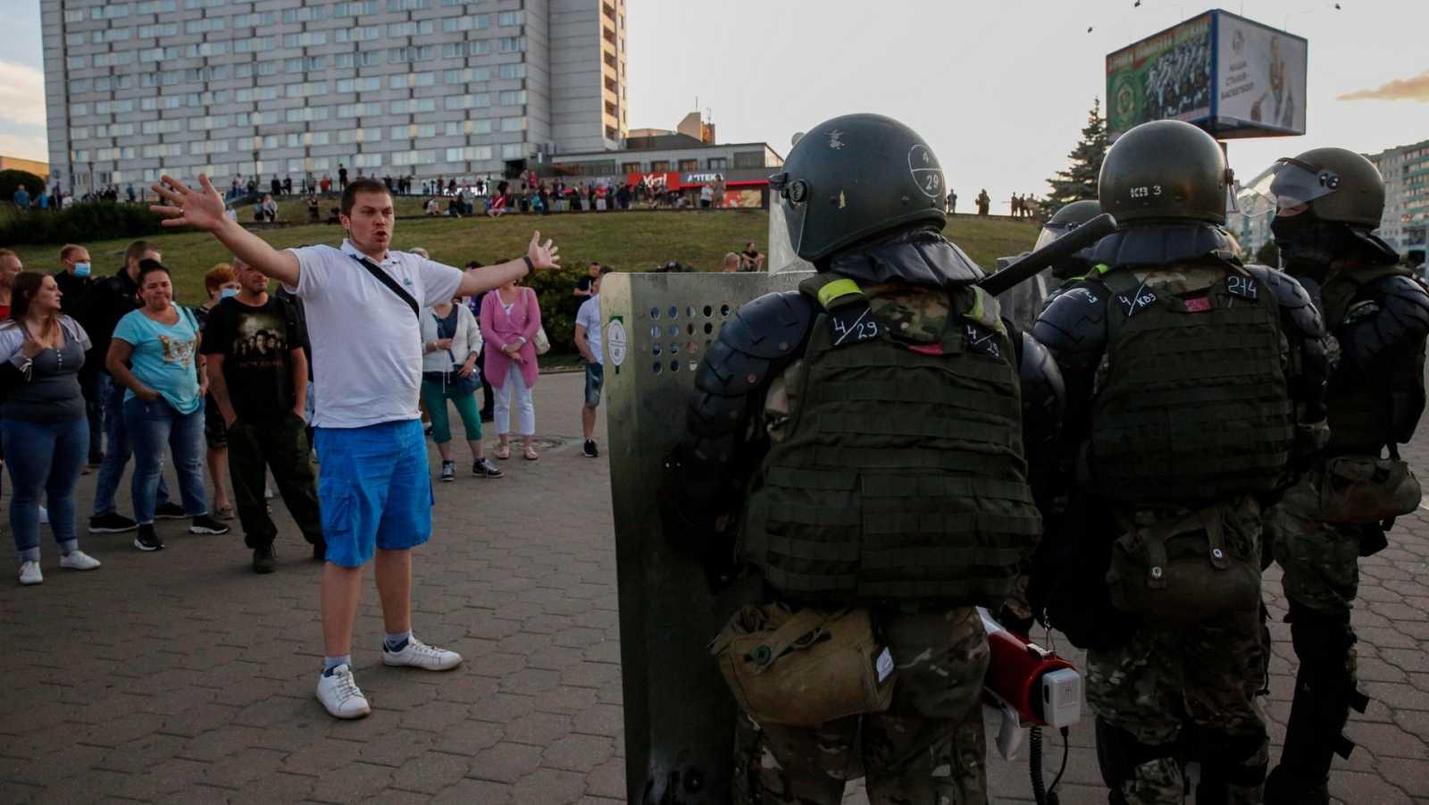 Un hombre habla con miembros del Ejército durante las protetas en Bielorrusia tras las elecciones