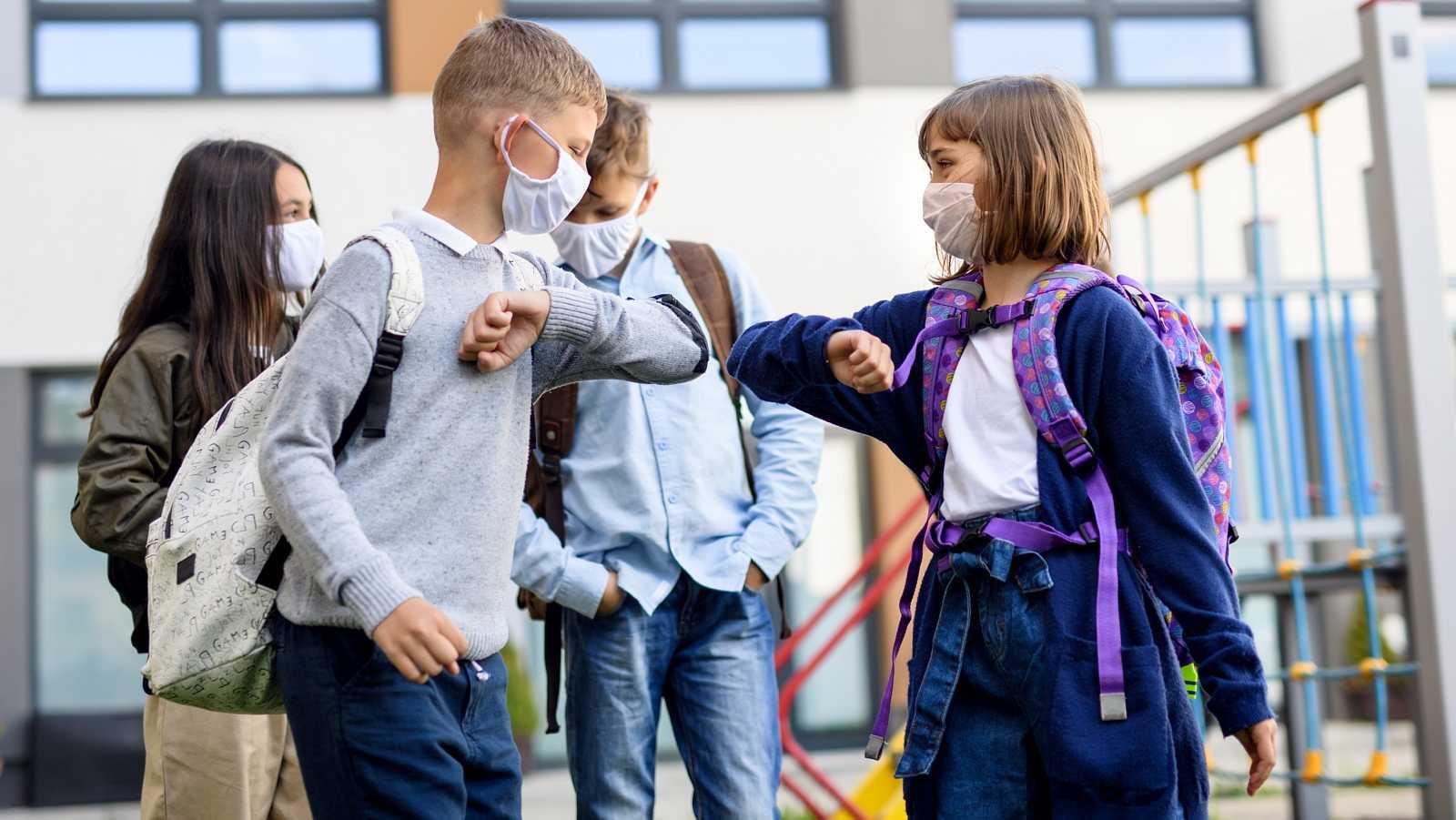Dos niños se saludan con el codo en la puerta de un colegio en la vuelta al cole tras el confinamiento por el coronavirus.