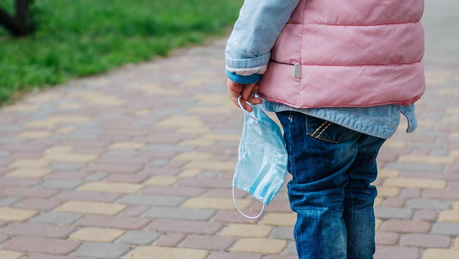 Una niña sostiene una mascarilla mientras camina por la calle.