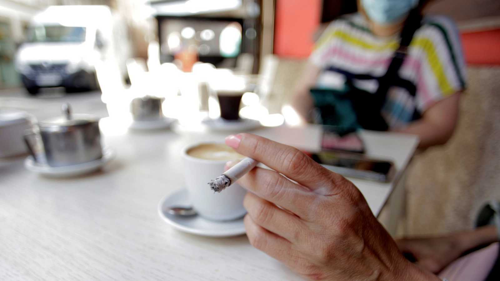 Una mujer fuma en la terraza de un bar
