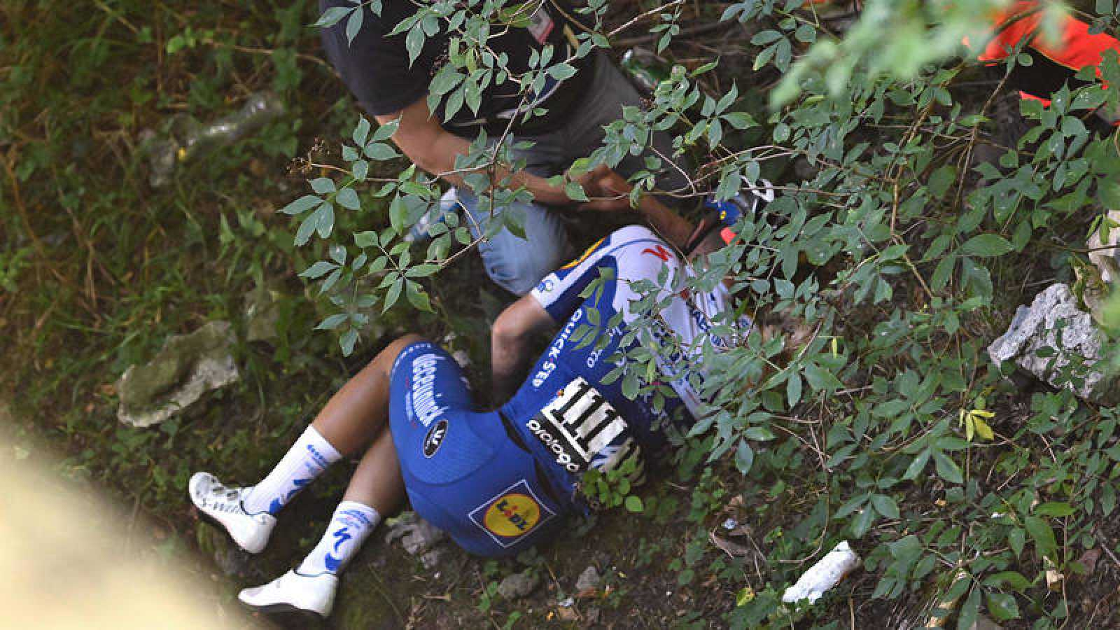 Evenepoel, tumbado de lado en el suelo, es atendido tras caerse por un puente