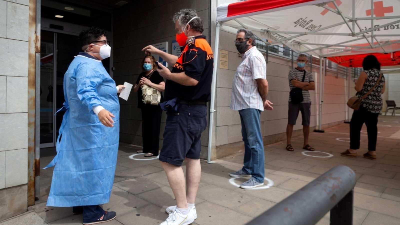 Un hombre habla con un sanitario a las puertas de un centro médico en Santa Coloma de Gramanet, Barcelona.