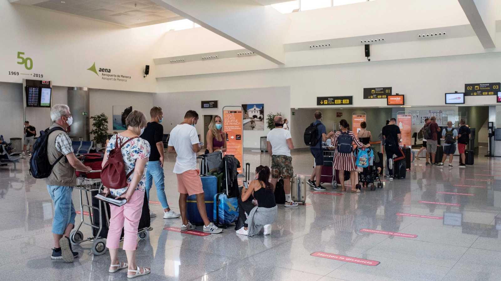 Varios turistas hacen cola en uno de los mostradores del aeropuerto de Mahón (Menorca).