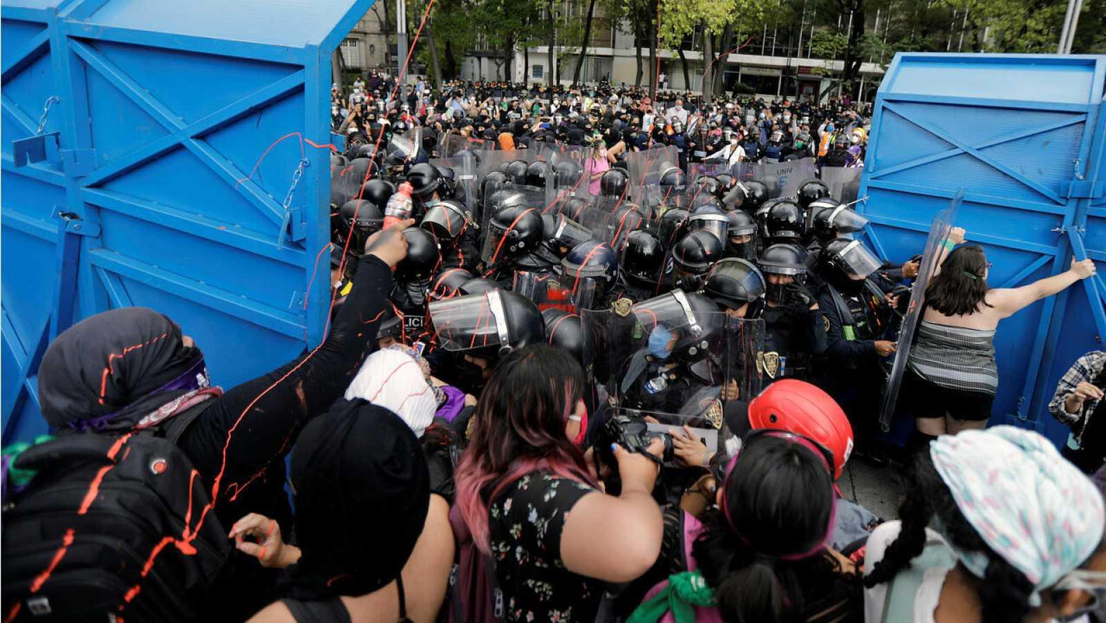 Manifestantes intentan romper una barricada mientras intentan marchar hacia un monumento durante una marcha exigiendo justicia para las víctimas de violencia de género y feminicidios en la Ciudad de México, México