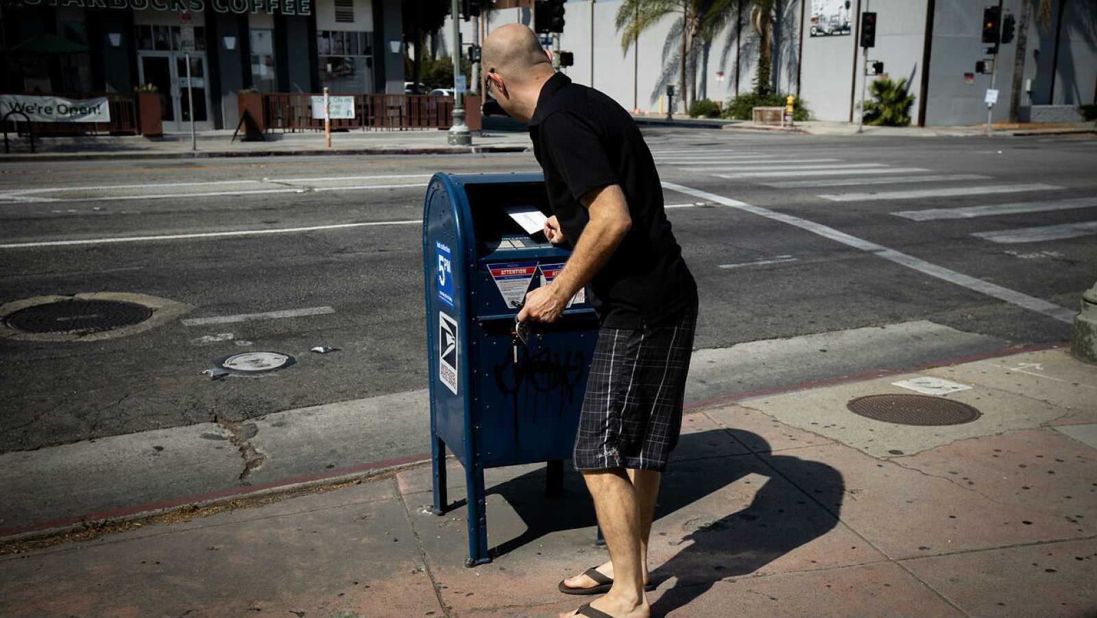 Un hombre arroja correo en un buzón de correo de USPS frente a una oficina de correos en Los Ángeles, California.