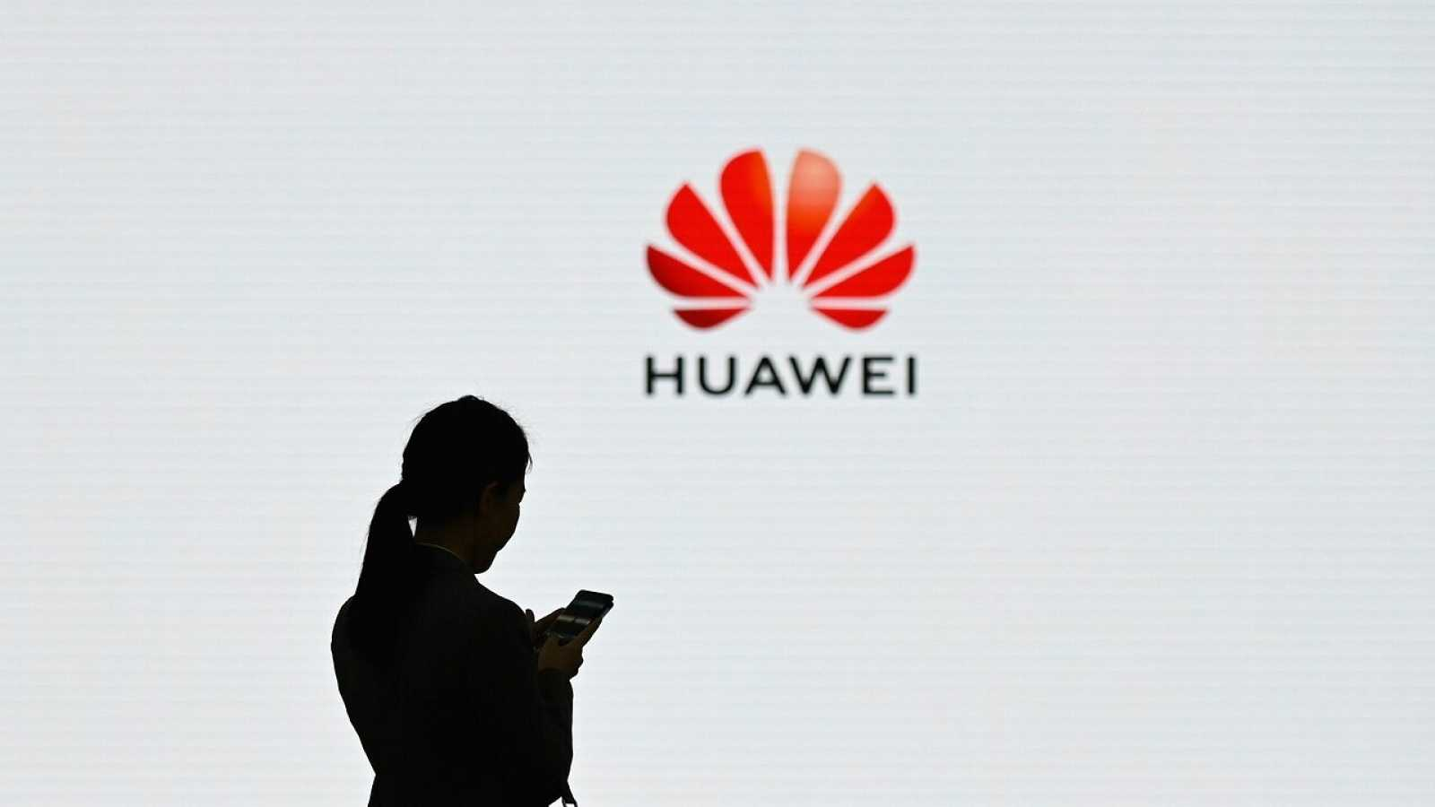 Una mujer utiliza su teléfono móvil frente al logo de Huawei
