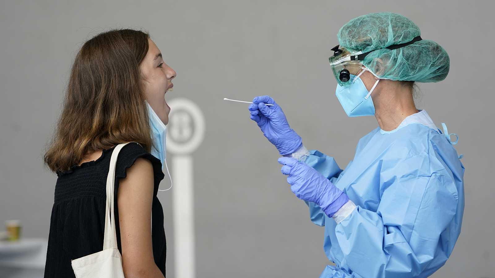 Una trabajadora sanitaria obtiene una muestra de una mujer para someterla a una prueba PCR.
