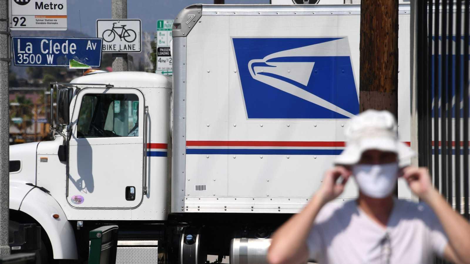 Un hombre camina frente a un camión del Servicio Postal en Los Ángeles