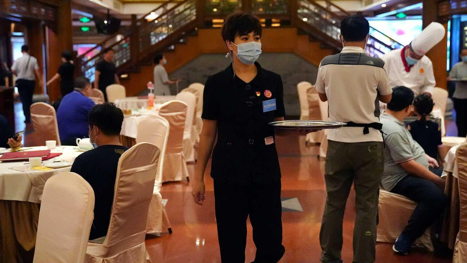 Un miembro del personal que también es supervisor contra el desperdicio de alimentos, sostiene una bandeja en un restaurante en Beijing, China.