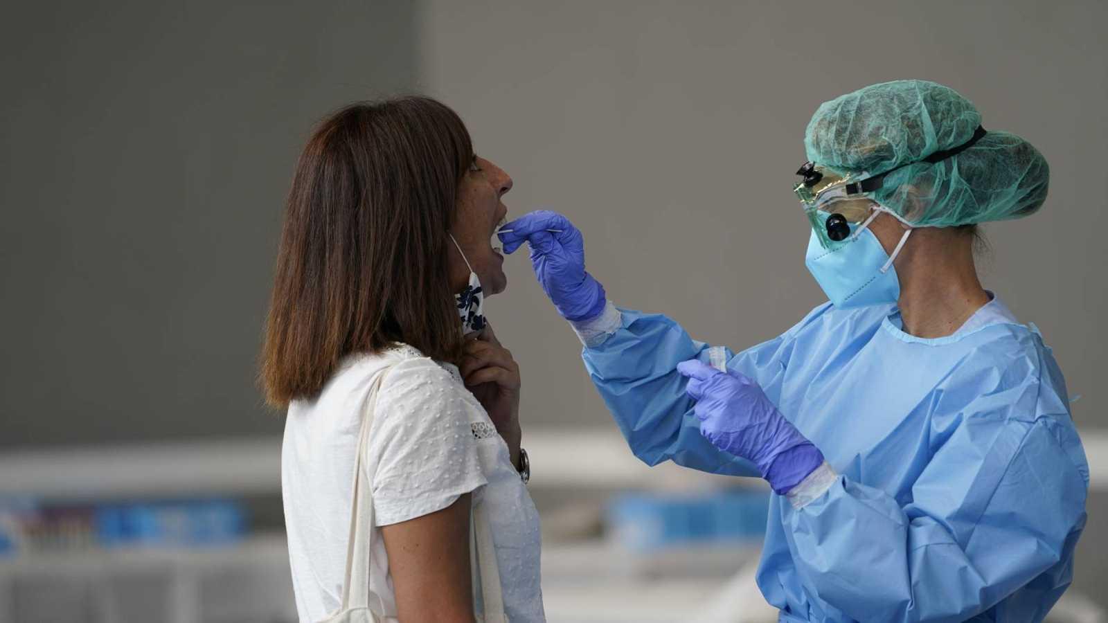 Una trabajadora sanitaria obtiene una muestra de una mujer para someterla a una prueba PCR
