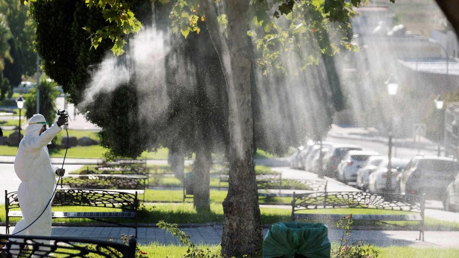 Un operario fumiga unos jardines en la Puebla del Río