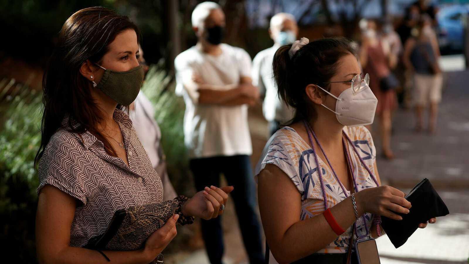 Varias personas esperan su turno para hacerse una PCR en el Centro de Salud de Los Ángeles, en el distrito de Villaverde, en Madrid.