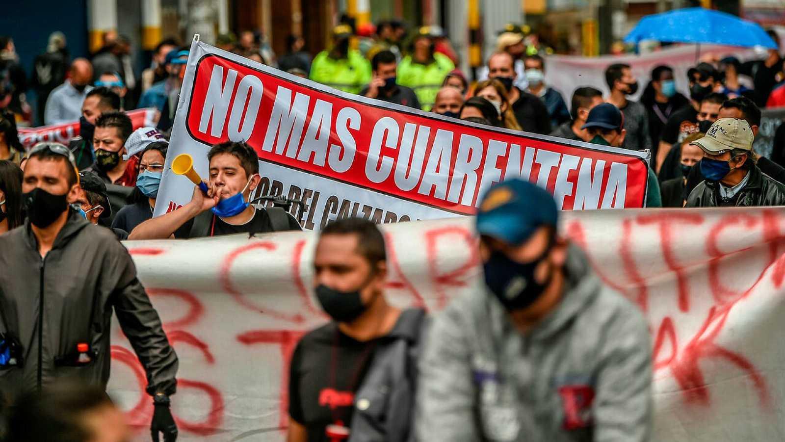 Comerciantes con mascarilla participan en una protesta en Bogotá para pedir la reapertura de comercios y el fin del confinamiento.