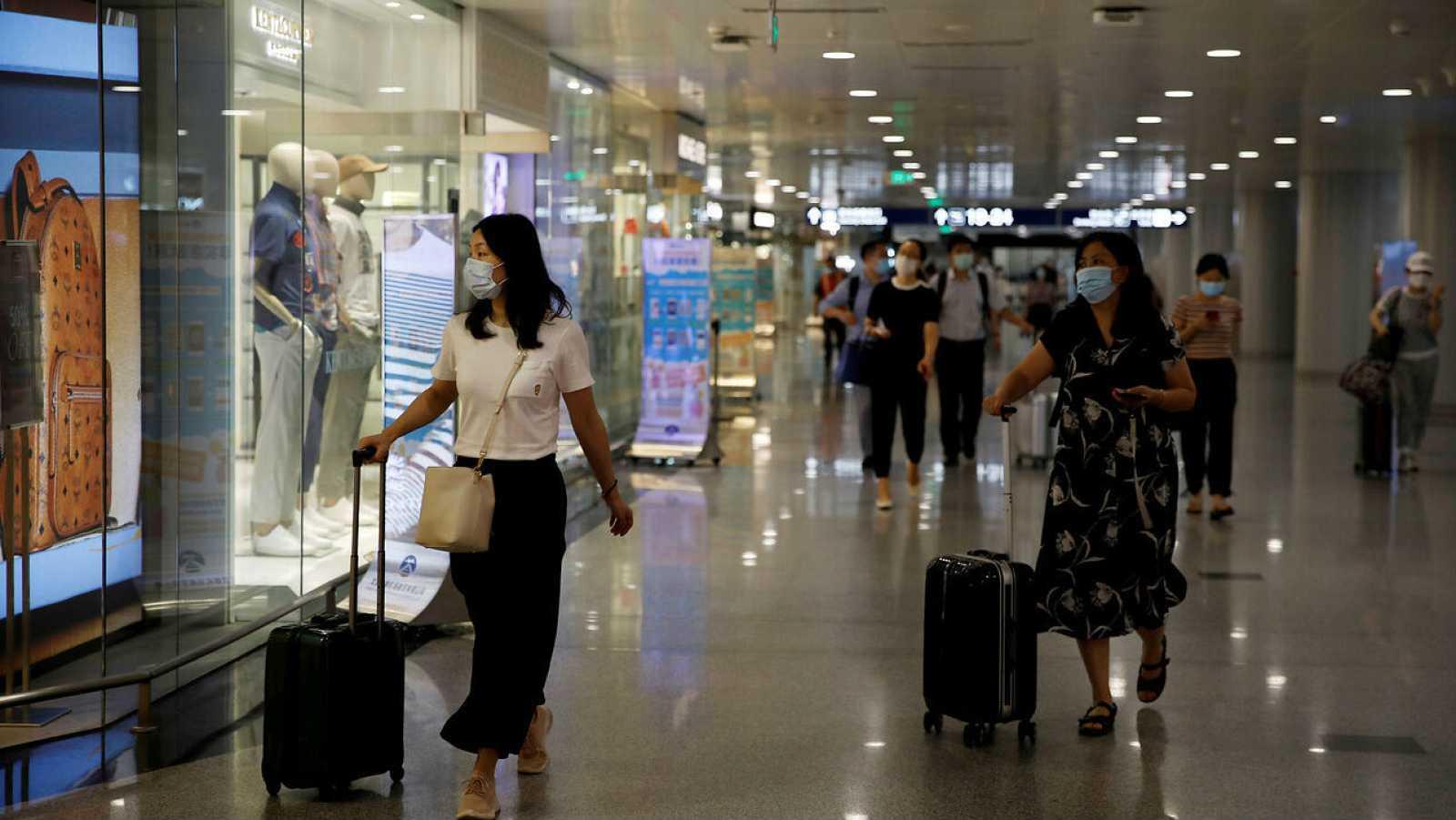 Viajeros con mascarillas pasan por las tiendas minoristas en el Aeropuerto Internacional de Beijing Capital en Beijing, China.