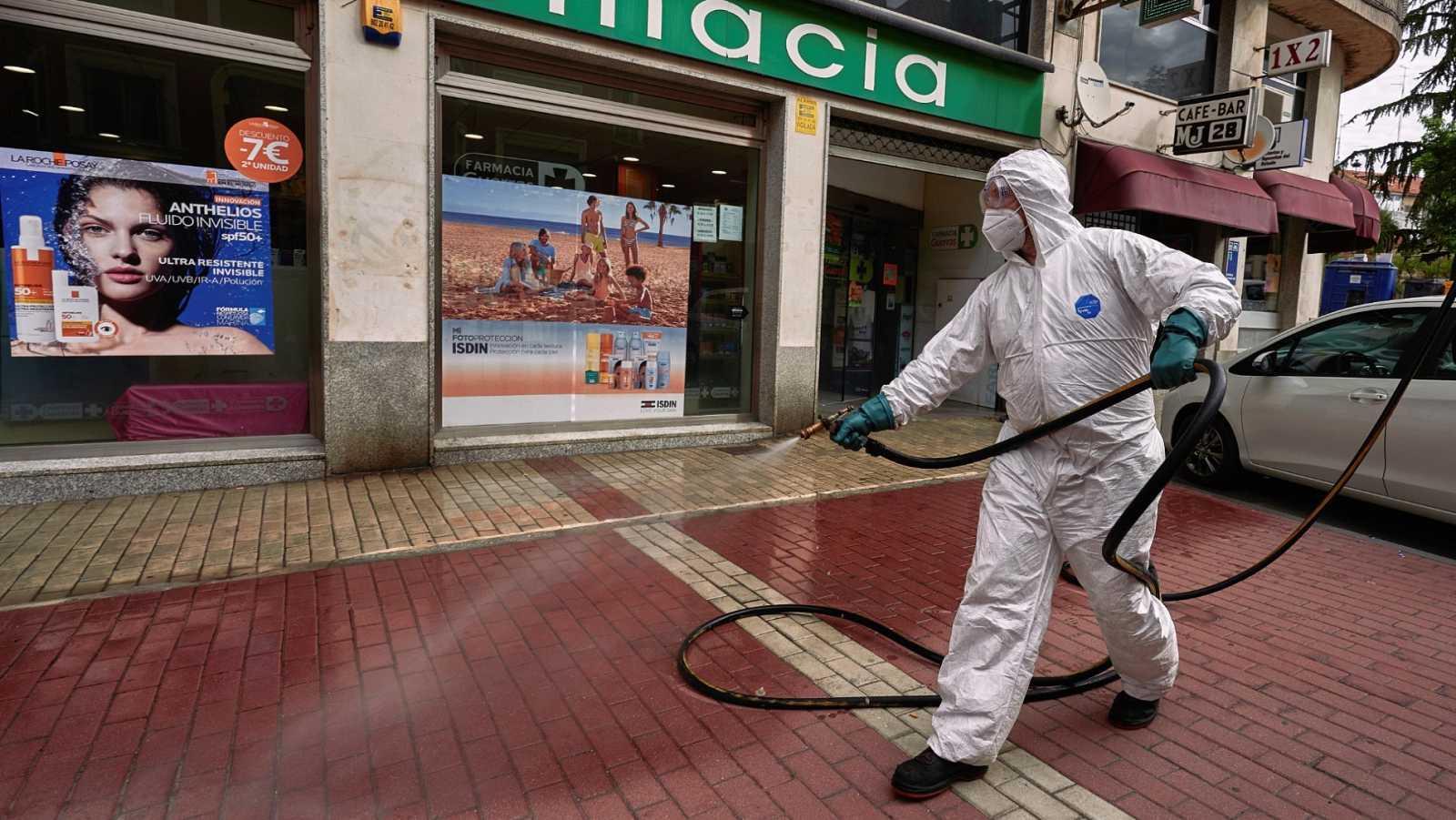 Un operario desinfecta la entrada de una farmacia en una calle de Ávila