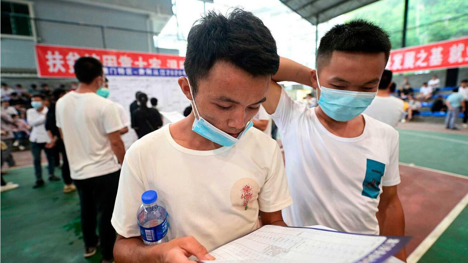 Personas llenando formularios en una feria de empleo en Congjiang, en la provincia de Guizhou, suroeste de China.