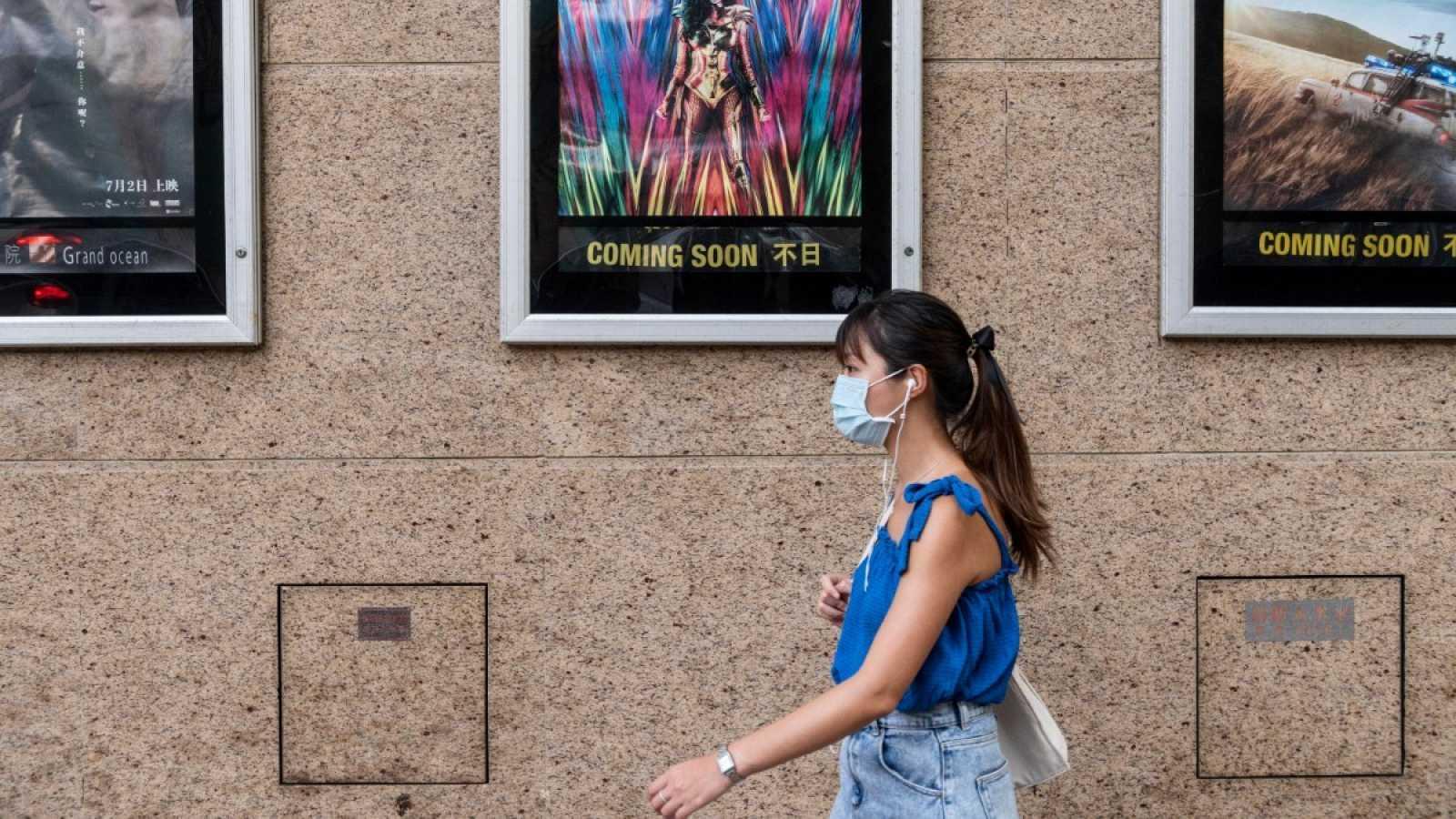 Una mujer con mascarilla pasa por delante de un cine en Hong Kong