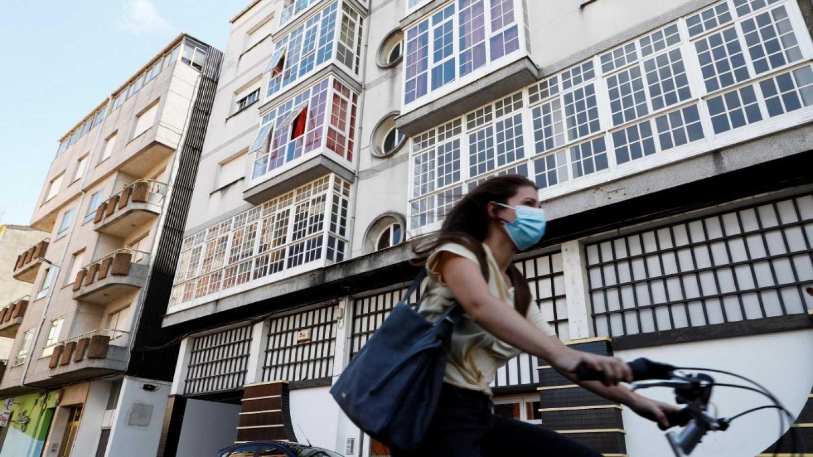 Una mujer monta en bicicleta junto a un edificio confinado en la localidad lucense de Monforte de Lemos