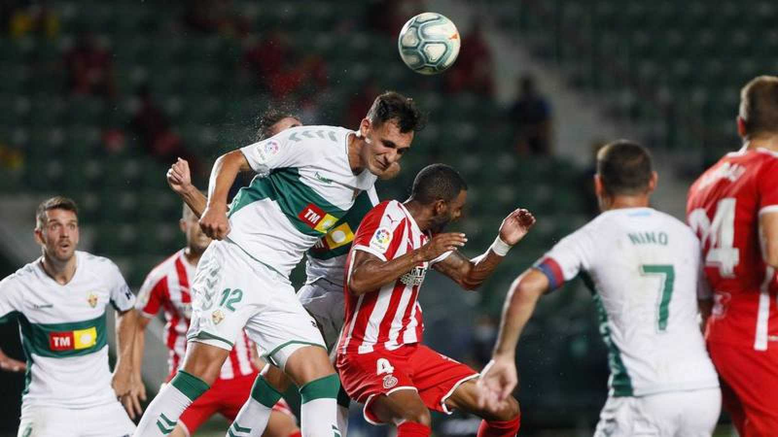 El defensa del Elche Dani Calvo (i) salta por el balón con Jonás Ramalho, del Girona.